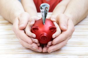lose up of father and son hands holding red piggy bank representing a social security attorney chicago