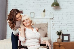 elderly woman smiling in a wheelchair with her daughter after speaking with a trusted libertyville social security lawyer