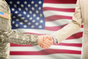 American soldier in uniform and Chicago civil rights lawyer in suit shaking hands with national flag on background.