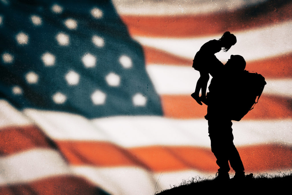 An American soldier lifting a child into the air representing how our VA benefits attorney can help you get the benefits you deserve