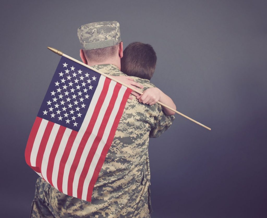A young child is hugging his father representing how our VA benefits attorney near me can help you make sure you get the right type of benefits