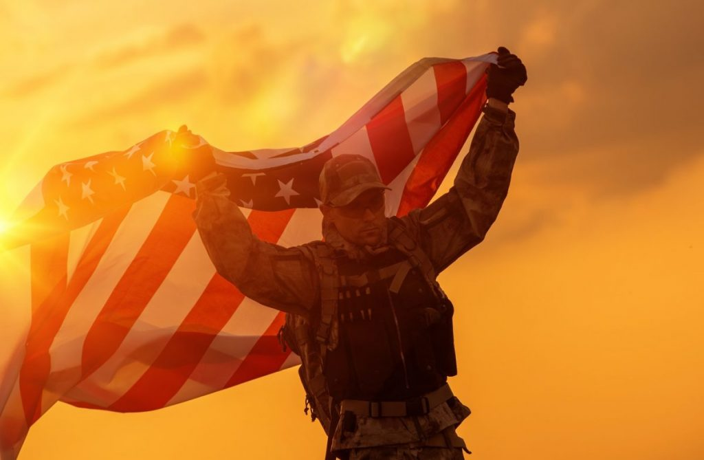 Soldier with American flag representing how our Indianapolis veterans benefits lawyer can assist you with your case