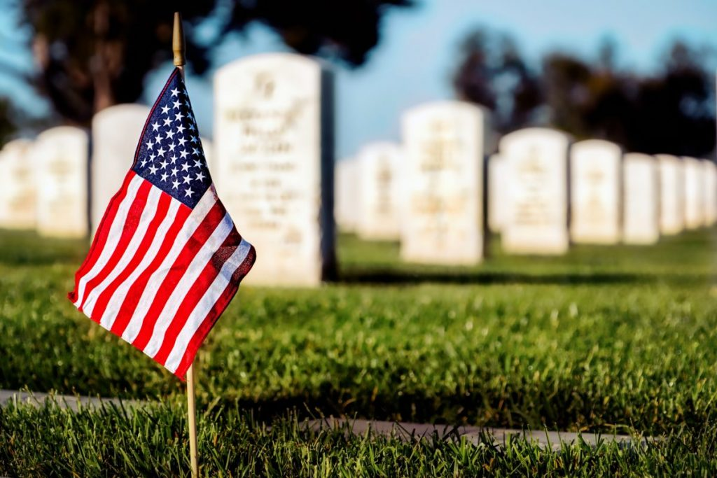 Flag on a veteran's grave representing how our Northwest Indiana veterans benefits lawyer can assist you with your legal issue