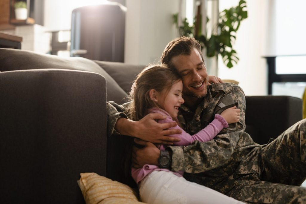 Army father and daughter hugging on couch representing how our East Chicago VA lawyer can help you receive your benefits