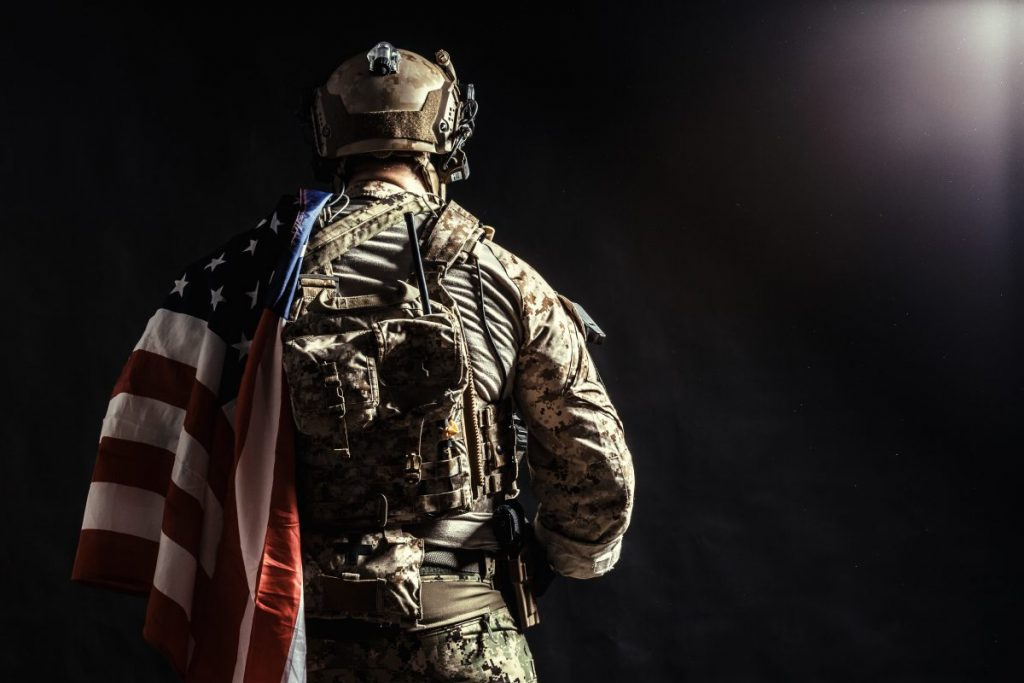 soldier with flag representing how our Champaign VA attorney can help make sure you get the benefits you deserve