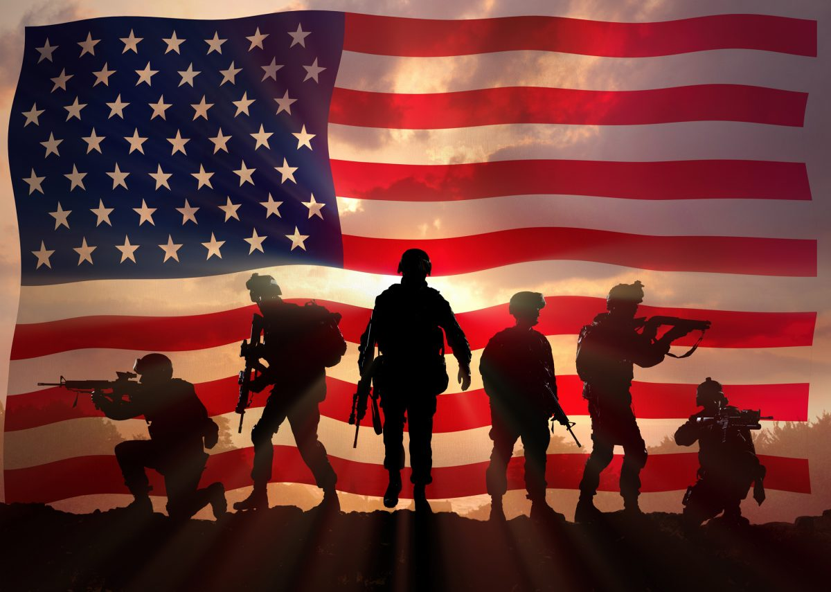 Silhouette of soldiers with American flag behind them. For your correct VA benefits meet with LaSalle County Veterans Disability Attorney.