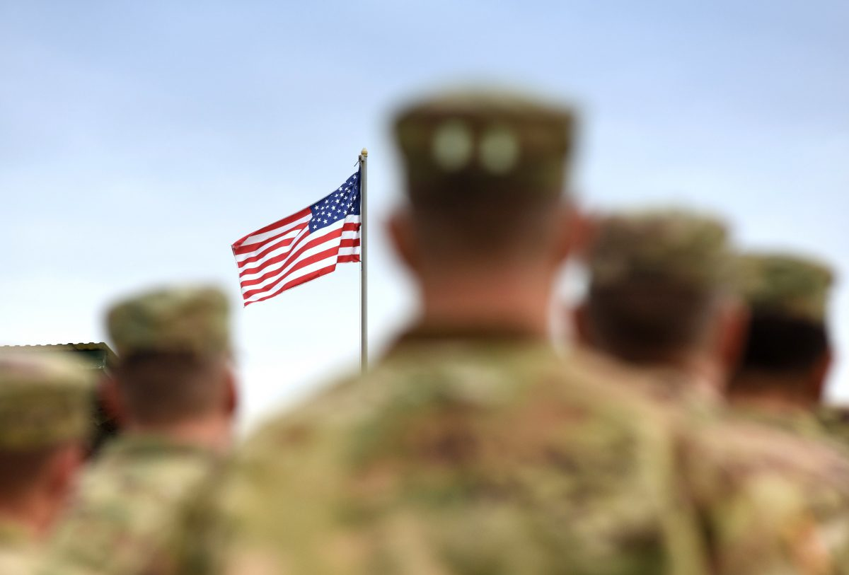 Soldiers standing looking at American flag, for reliable VA coverage speak to Veterans Benefits Attorneys Lake County.