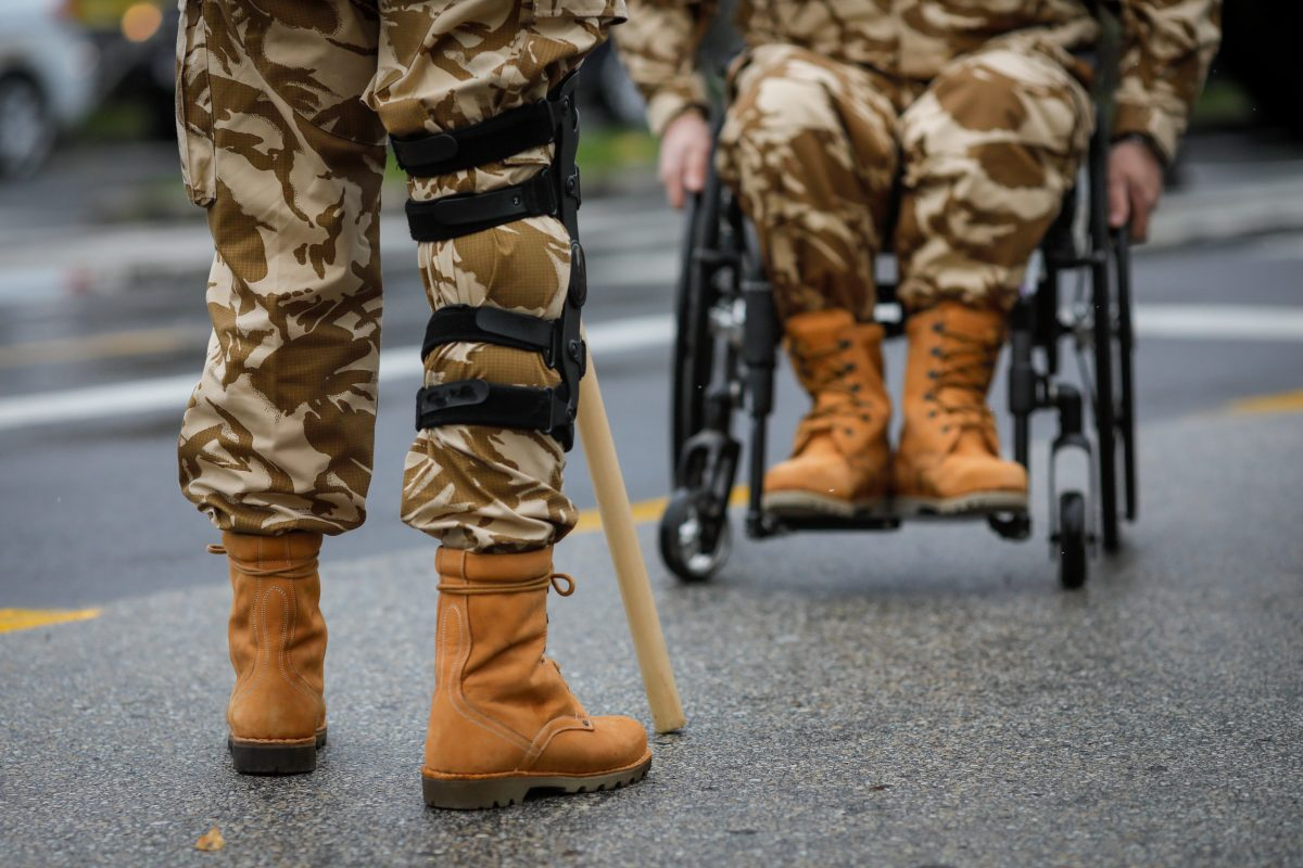 Details with an army veteran soldier, injured and disabled, sitting in a wheelchair dressed in his military desert camouflage uniform in need of Northbrook veterans benefits attorney