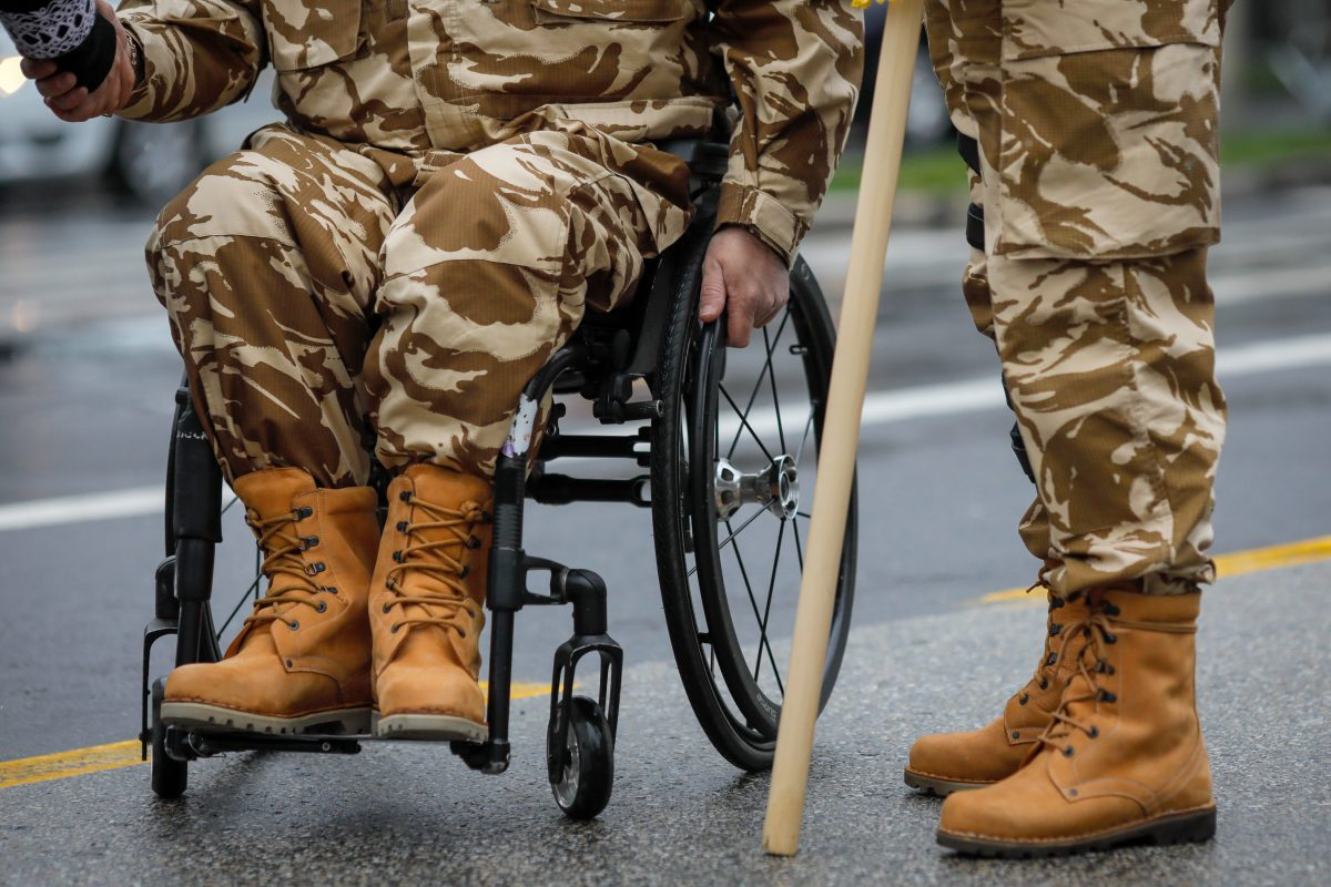 Details with an army veteran soldier, injured and disabled, sitting in a wheelchair dressed in his military desert camouflage uniform in need of a Bolingbrook Veterans Benefits Attorney