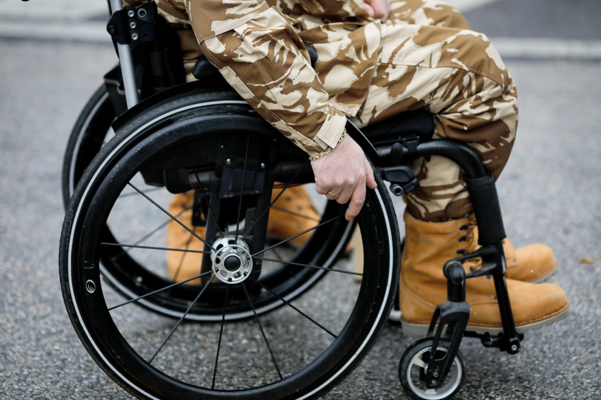 Details with an army veteran soldier, injured and disabled, sitting in a wheelchair dressed in his military desert camouflage uniform seeking cook county VA benefits
