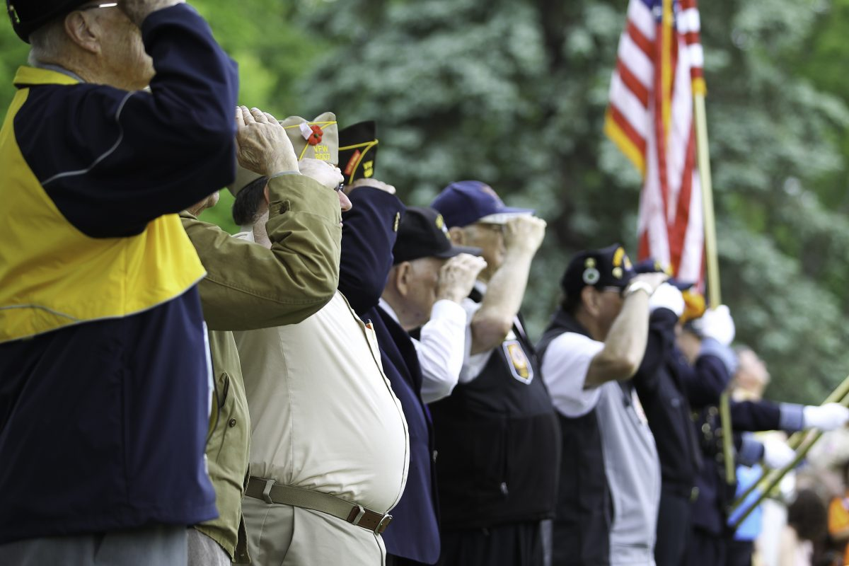 A row of veterans saluting flag, for advice on your denied claim speak to Evanston VA Disability Lawyers.
