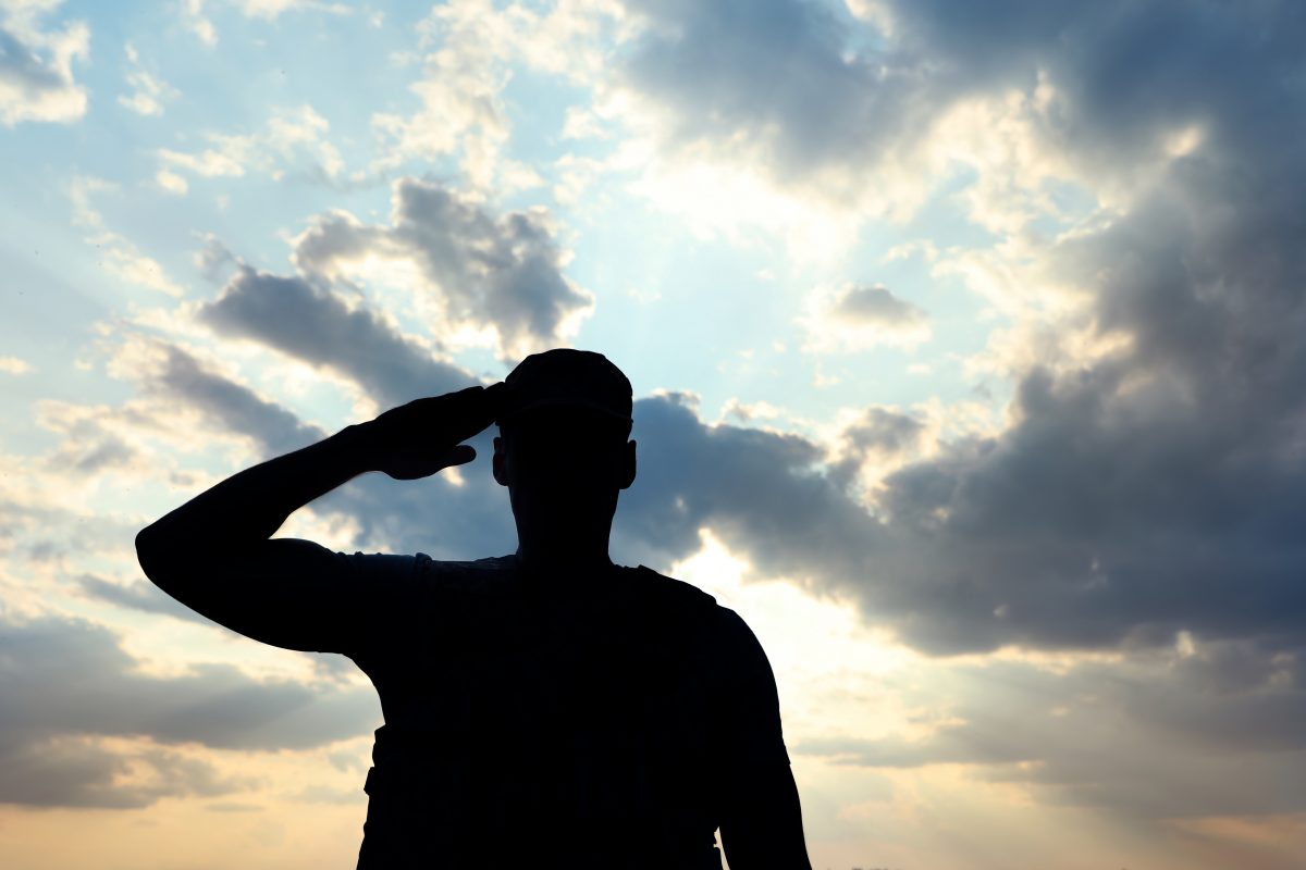 A soldier in uniform saluting with cloudy sky behind him, if dealing with the wrong insurance coverage visit a Cook County VA Benefits Appeal Lawyer
