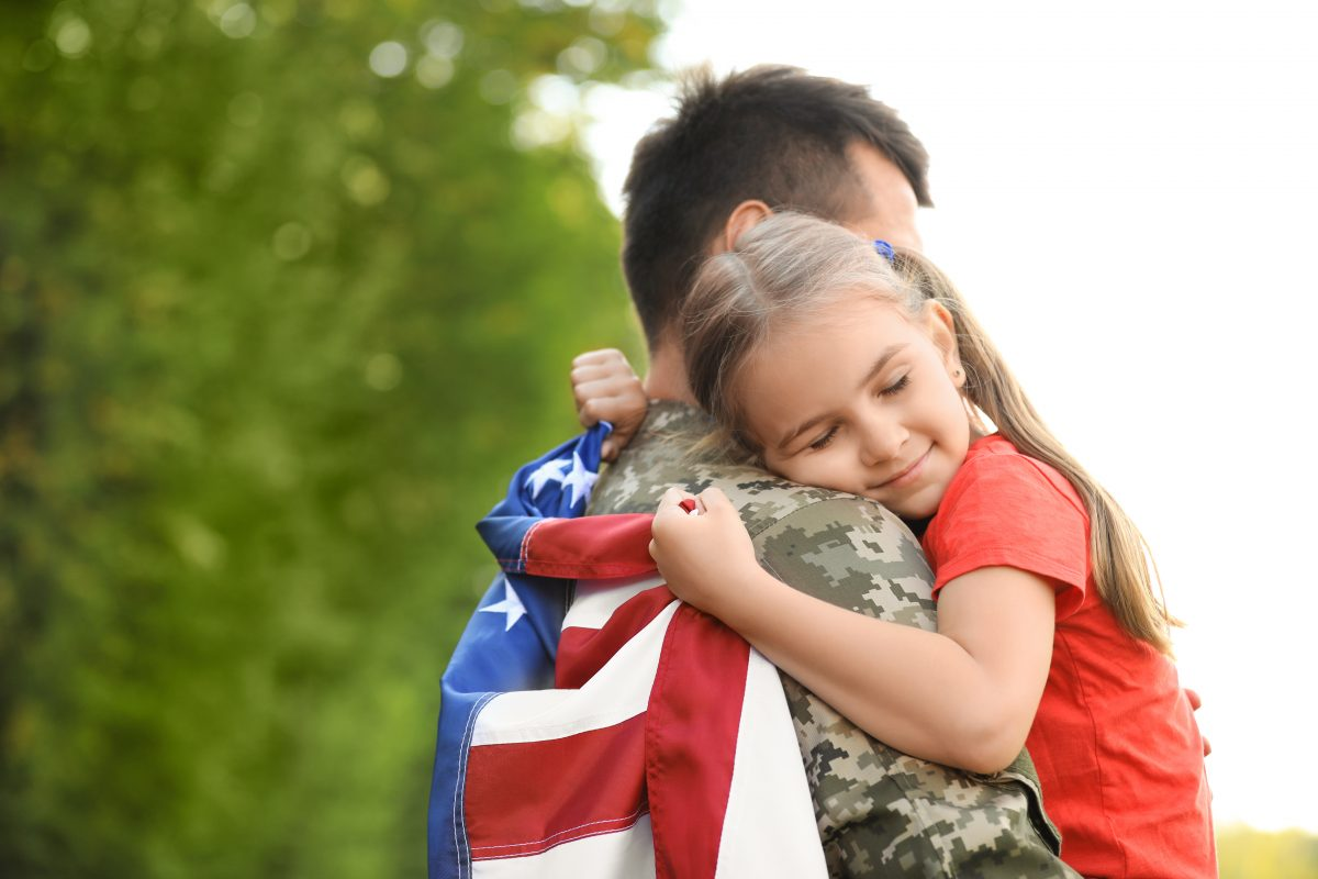 A dad in military uniform with his daughter hugging him, if your health insurance coverage has beenDenied VA Disability Benefits Lawyer in Illinois.denied, meet with v