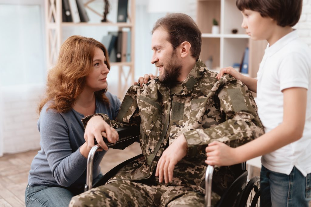 A veteran is home in a wheelchair with his family, to receive your correct benefit payments consult with VA Disability Benefits Attorney Near Me.