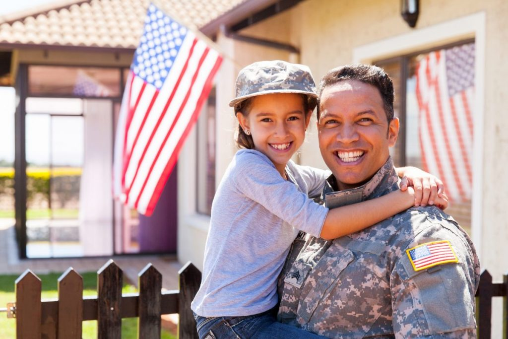 An army vet with his daughter outside their home, contact rland Park Veterans Disability Attorneys to receive your rightful benefits.