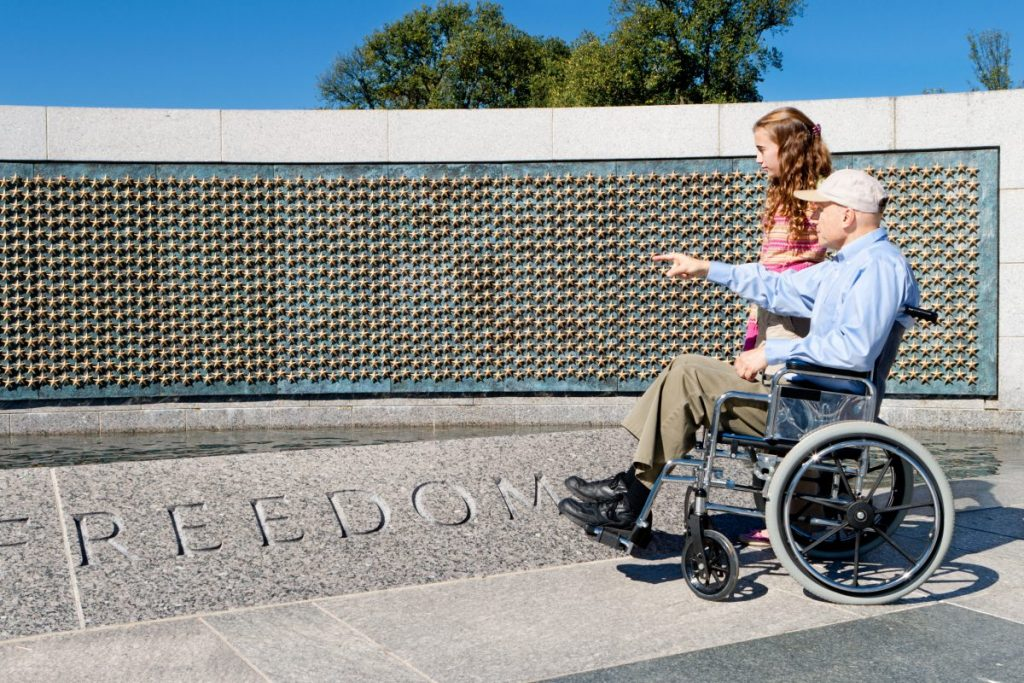 An older man in a wheelchair pointing showing granddaughter the WW II memorial, a Peoria VA Disability Attorney can help with your terminated benefits.
