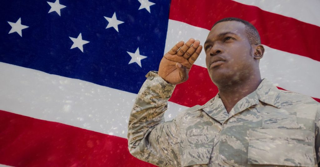 Uniformed military man saluting with US flag behind him, when suffering from the wrong coverage from your injury, meet with Lake County, IL VA Disability Lawyer.