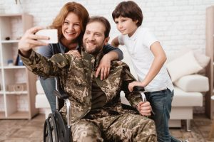 Veteran in a wheelchair posing for picture with his family, when your benefits have been denied speak to Veterans Benefits Attorney Aurora.