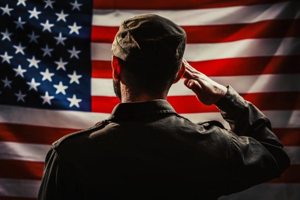 A soldier in uniform saluting American flag, the Cook County Veterans Benefits Attorney will assist with your insurance coverage.