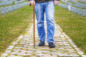 Man walking with a cane in a cemetary, the Illinois Veterans' Disability Appeals Attorney will assist your insurance claim case.